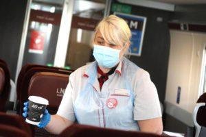 A woman serves a drink onboard a train