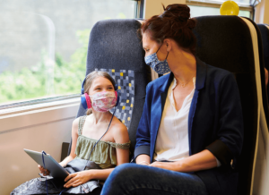 A woman and a young girl sit next to each other on a train, both wearing face masks