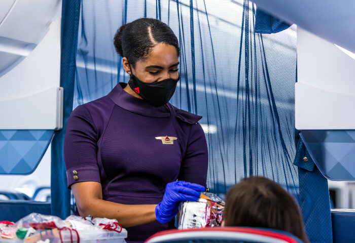 An airline attendant hands a product to a customer.
