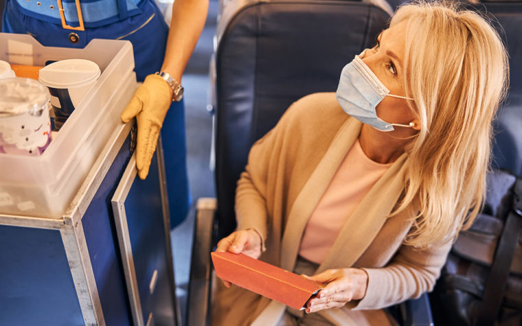 A woman with a face mask on looks up to order from a flight attendant on a plane
