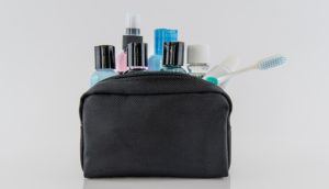 An amenity kit with plastic bottles and toothbrush